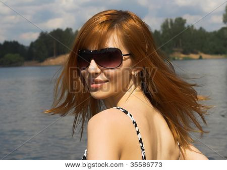 Photograph of a beautiful woman with sunglasses on the beach