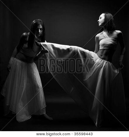 Portrait of two girls in white raiment dancing in semi-darkness ...