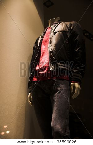 Close-up shot of the store window with a mannequin dressed in a fashionable clothes