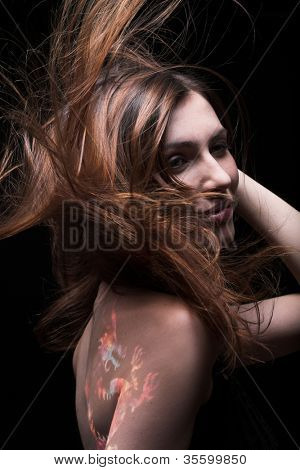 Studio portrait of a young beautiful girl with paint on her body and wind in her hair
