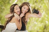 foto of two women taking cell phone  - Two Attractive Mixed Race Girlfriends Taking Self Portrait with Their Phone Camera Outdoors - JPG