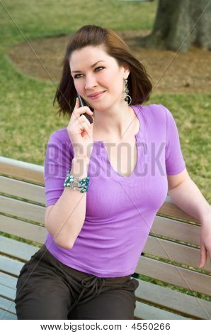 Pretty Girl Sitting On Park Bench Talking W/ Cell Phone