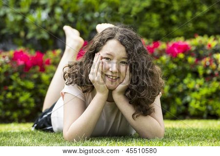 Young Girl With Big Smile While Lying Down On Lawn Outside