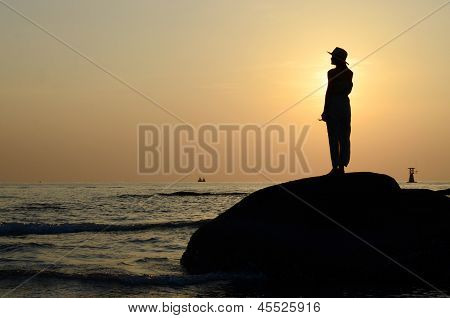 Beautiful Asian Woman Standing On Stone Silhouetted The Sunrise In Morning Scene.