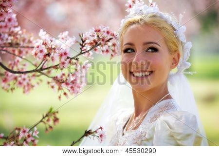 Bride Smiles Next to Cherry Blossom Tree