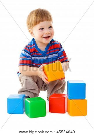 Little boy playing with colorful cubes
