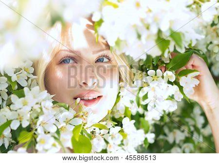 Closeup beautiful woman among blossom apple tree