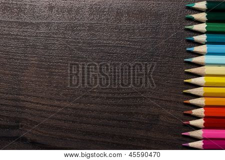 colorful pencils on dark brown table background