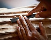 picture of woodcarving  - Hands woodcarver with the tool close up - JPG