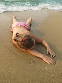Cute Young Girl Lying On A Sandy Beach