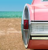 stock photo of muscle-car  - Vintage pink car tail light detail on the beach - JPG