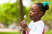 stock photo of innocence  - Outdoor portrait of a cute young black girl blowing a dandelion flower  - JPG