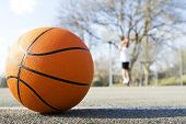 stock photo of slam  - Basketball close up with a male basketball player in the blurred background - JPG