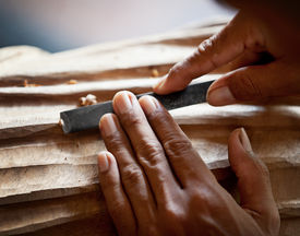foto of woodcarving  - Hands woodcarver with the tool close up - JPG