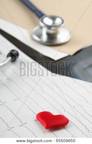A file folder, a stathoscope and a heart on ekg