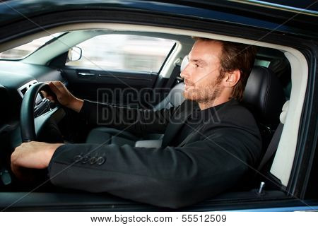 Young man in black driving luxury car, smiling.