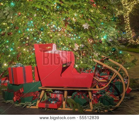 Christmas Gifts And Sled Under The Tree
