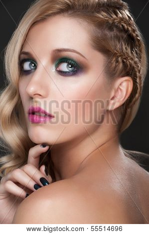 Portrait of young beautiful woman with bright fashion makeup, manicure and creative hairstyle with tress