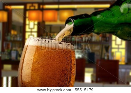 Pouring beer into glass with bar in background
