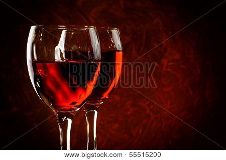 Two glasses of red wine with abstract red background