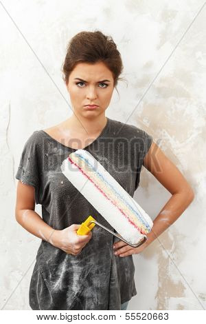 Disgruntled young brunette woman doing wall painting