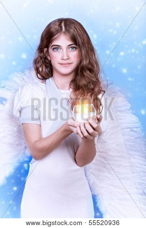 �?��?�¡ute angel, portrait of beautiful teen girl wearing fluffy wings and holding in hands candle on snowing background, purity and innocence conception