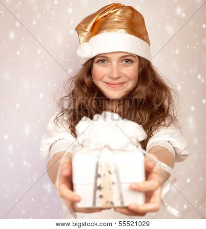 Santa girl offers gift box, cute teenager wearing shiny hat isolated on beige snowing background, Christmastime surprise