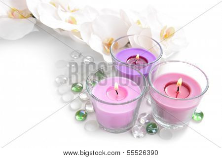 Beautiful colorful candles and orchid flowers, isolated on white