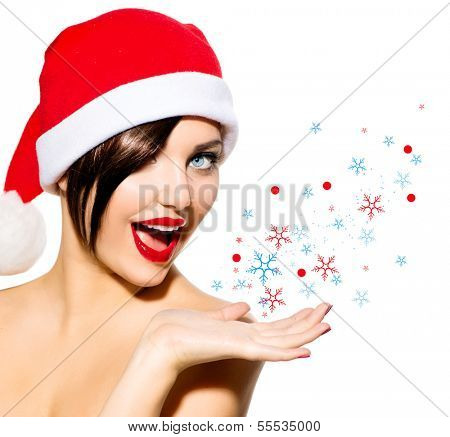 Christmas Woman. Beauty Model Girl in Santa Hat isolated on White Background. Funny Laughing Surprised Woman Blowing Snow. Open Mouth. True Emotions. Red Lips. Beautiful Holiday Makeup.