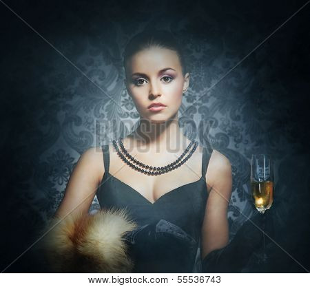 Attractive young lady with the glass of sparkling wine over the retro background
