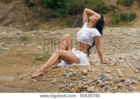 Sexy Girl In Denim Shorts And White Shirt Sitting By The Countryside Road