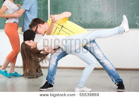 High school student in classroom surrounded with his jumping friends