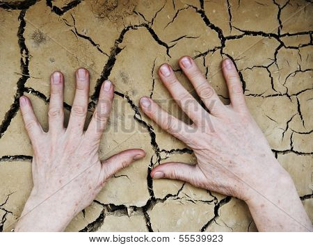 Human hands on cracked clay wall