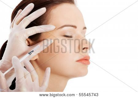 Beautiful woman's face is being prepareg to plastic surgery. Isolated on white.