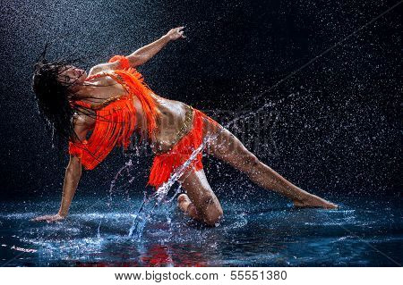 Woman Dancing Under Rain In Orange Dress. Studio
