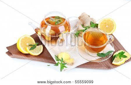 Kettle and cup of tea with ginger on napkin isolated on white