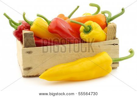 Red,yellow and green sweet peppers (capsicum) in a wooden crate on a white background