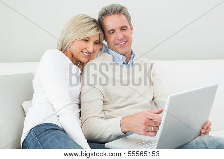 Happy casual couple using laptop in the living room at home