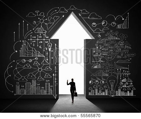 Silhouette of businesswoman against black wall with key hole