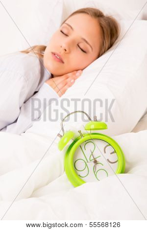 Beautiful Woman Sleeping With Alarmclock On The Bed