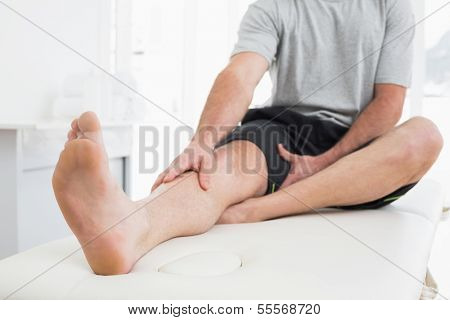 Low section of a young man with his hands on a painful leg while sitting on examination table