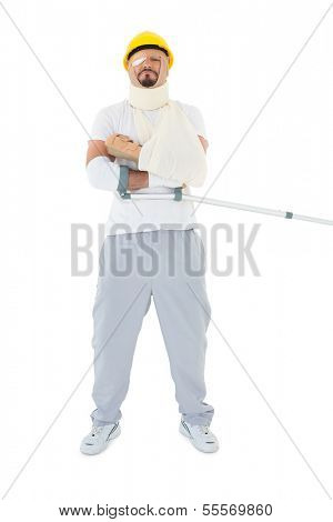 Full length of a young man in hard hat with broken hand and crutch over  white background