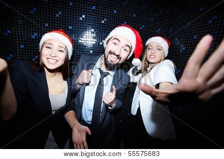 Portrait of joyful colleagues in Santa caps dancing at Christmas party