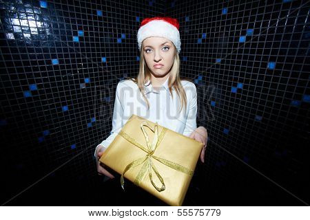 Portrait of displeased businesswoman in Santa cap holding Chistmas gift