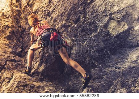 Athletic Woman Rockclimbing At Sunset