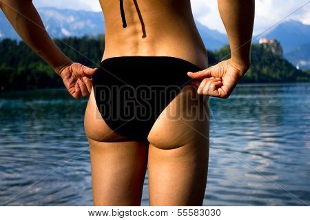 Rear View Of Sexy Woman Adjusting Her Swimsuit