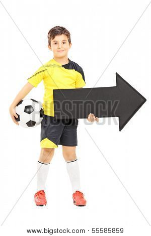 Full length portrait of a smiling boy in sportswear holding a soccer ball and black arrow pointing right isolated on white background