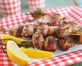 stock photo of souvlaki  - Souvlaki on rosemary sticks with lemon on a paper plate - JPG