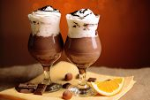 Tasty dessert with chocolate, cream and orange sauce, on wooden table, on lights background