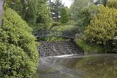 image of ironworker  - Ironwork bridge over small waterfall by lake in an English country garden - JPG